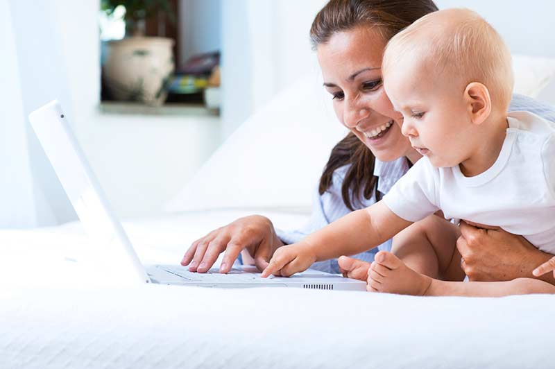 Woman and baby looking at a laptop.