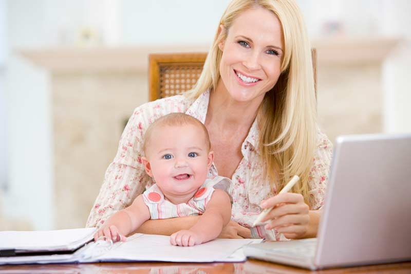 Woman holding a baby, working at a desk.