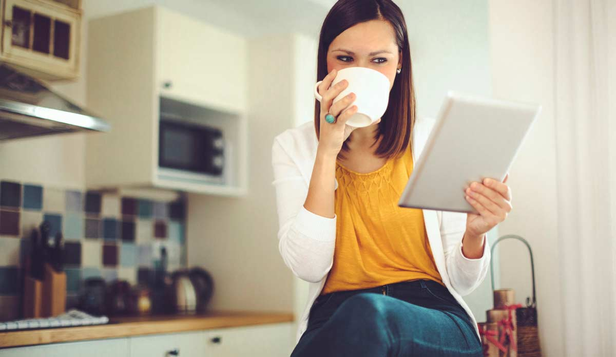 Young female sitting on a counter top drinking coffee while looking at her tablet.