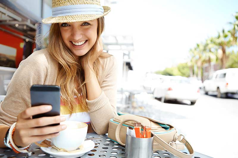 Woman dining outside looking at her phone